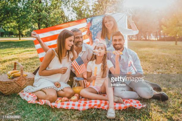 three generation family at picnic in park - fourth of july stock pictures, royalty-free photos & images