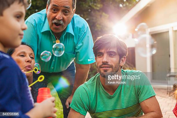 three generation family blowing bubbles in garden - older woman bending over stock pictures, royalty-free photos & images