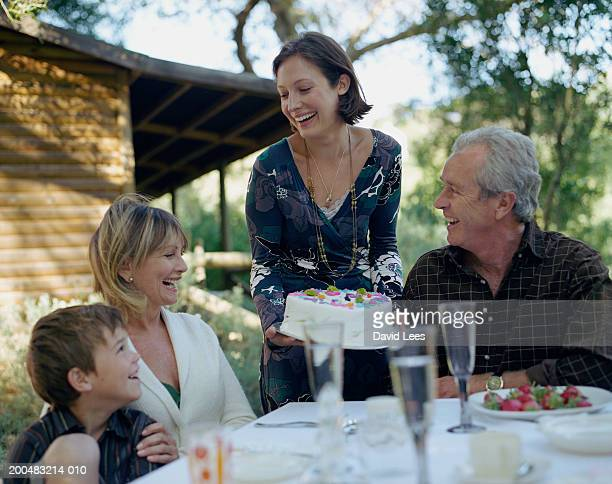 Three generation family celebrating birthday in garden