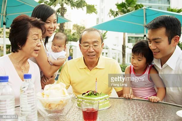 Three generation family celebrating grandfather's birthday