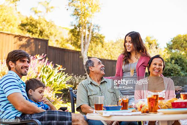 three generation family dining in garden - barbecue social gathering stock pictures, royalty-free photos & images
