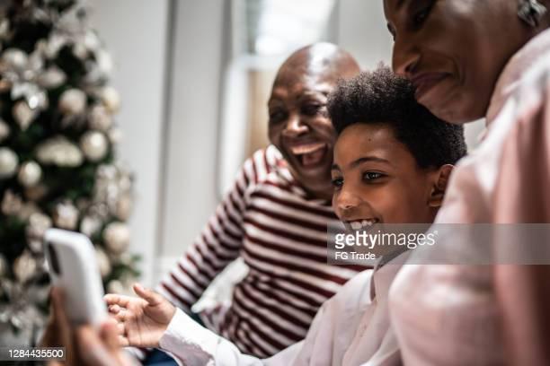 drei-generationen-familie macht einen videoanruf n smartphone zu hause - mother daughter webcam stock-fotos und bilder
