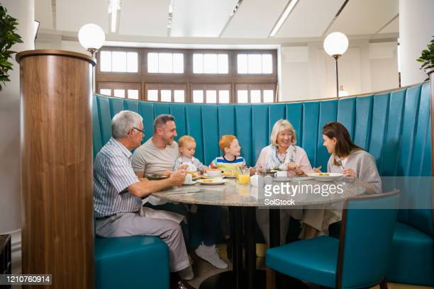 three generation family eating lunch in restaurant - medium group of people stock pictures, royalty-free photos & images