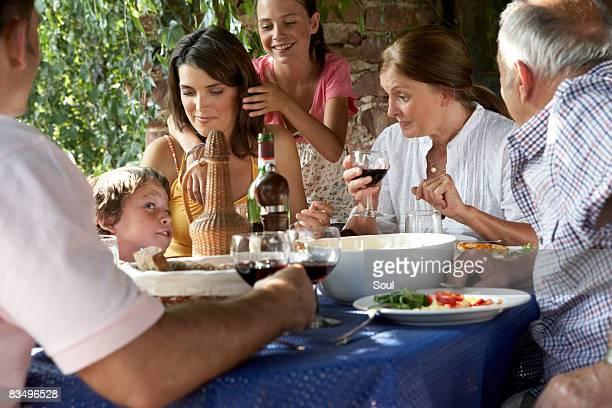 Tres generaciones familia comer un almuerzo al aire libre