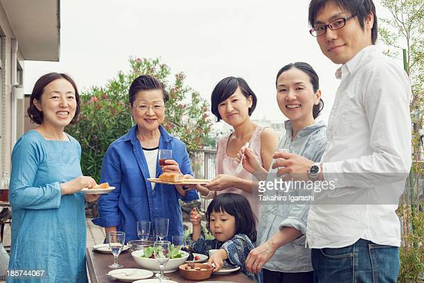 Three generation family eating outdoors,  portrait