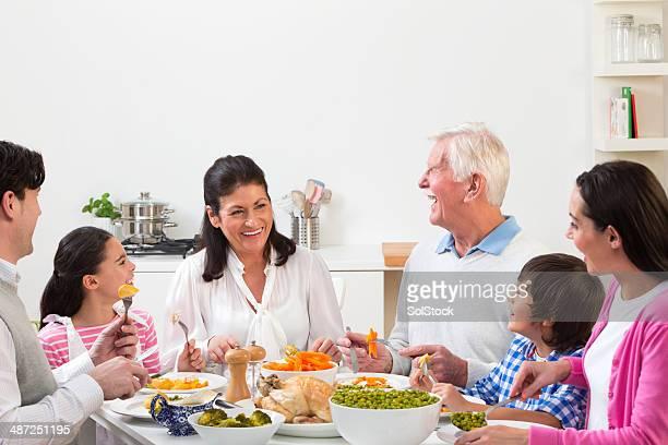 3 つの世代の家族の食べる日曜のロースト