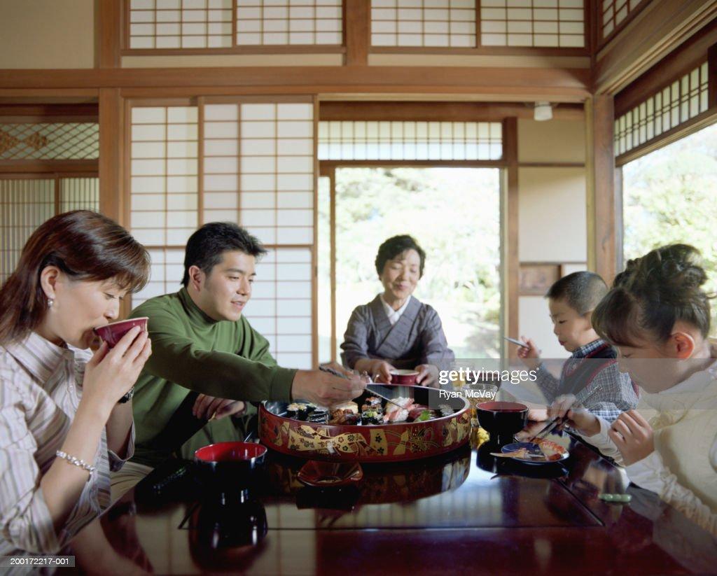 Three generation family eating sushi : Stock Photo