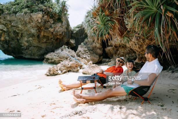 three generation family enjoying beach campsite, okinawa, japan - ippei naoi stock pictures, royalty-free photos & images