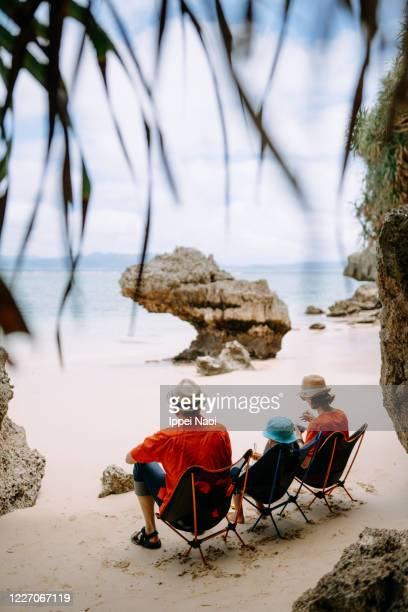 three generation family having lunch at beach campsite - ippei naoi stock pictures, royalty-free photos & images