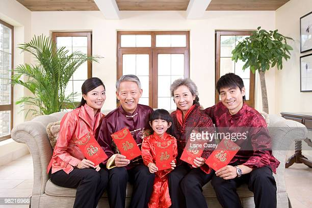Three generation family holding Chinese new year red envelop