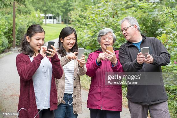 Three Generation Family Holding Smartphones to Play Augmented Reality Game