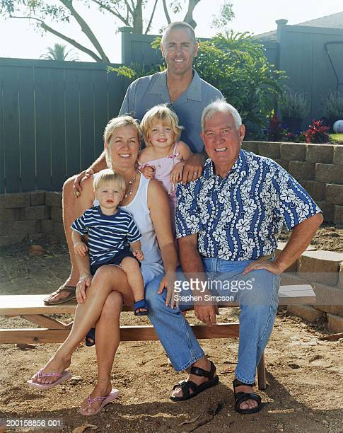 Three generation family in backyard of home, portrait