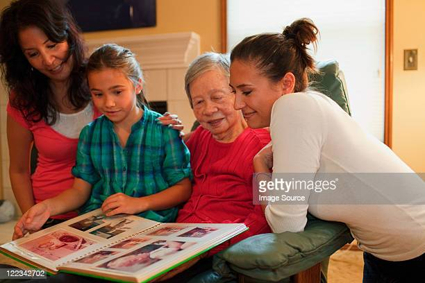 three generation family looking at photo album - great grandmother stock pictures, royalty-free photos & images