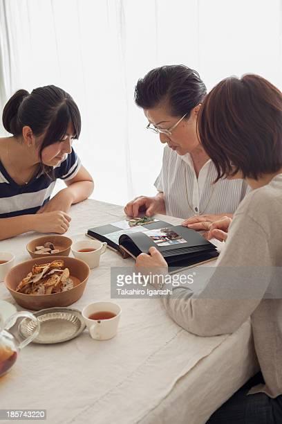 Three generation family looking at photograph album