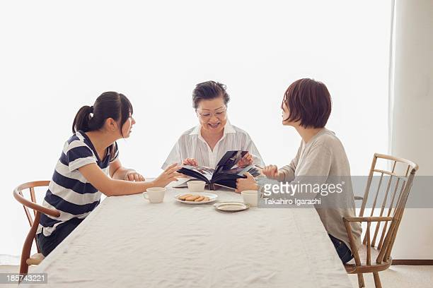 Three generation family looking at photograph album