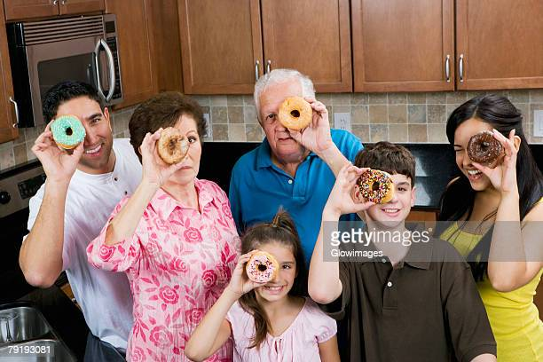 Three generation family looking through donuts