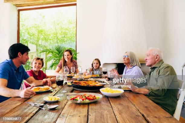 tres generaciones de familiares conversando durante la comida del mediodía - de origen español o portugués fotografías e imágenes de stock