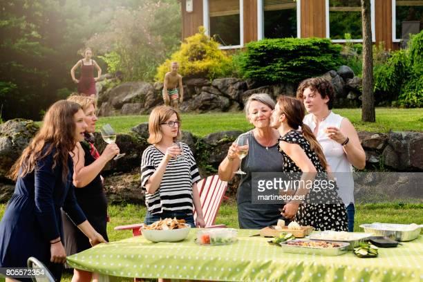 Three generation family of women preparing food outdoors.