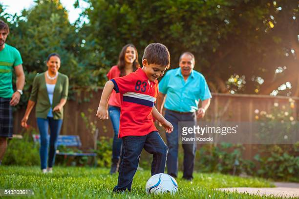 Three generation family playing football in garden