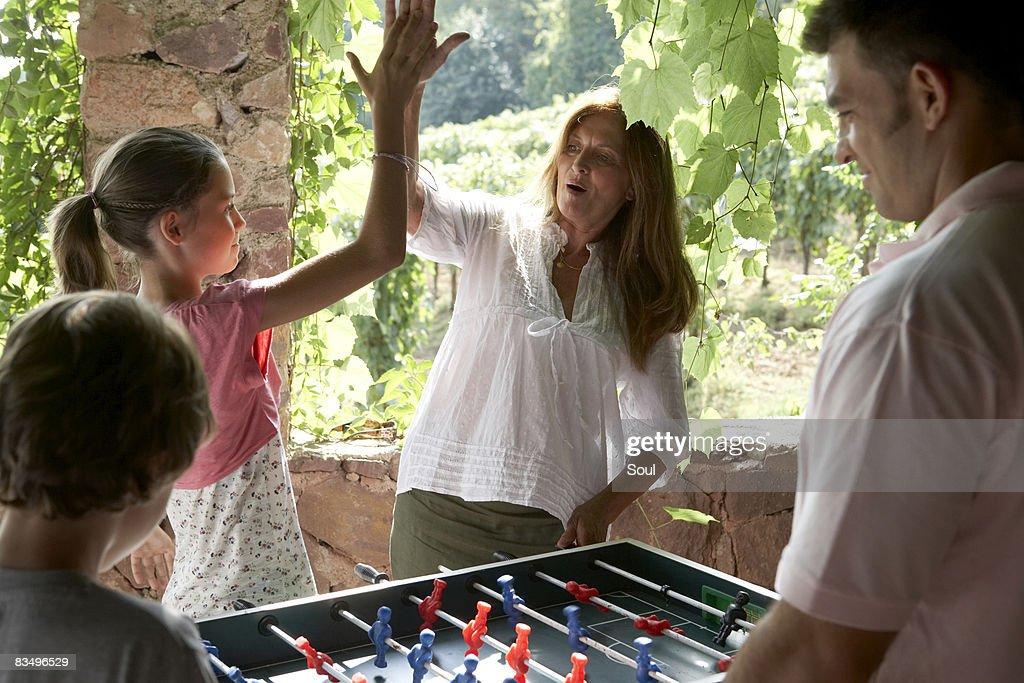 Tres generaciones familia jugando al fútbol de mesa : Foto de stock