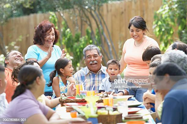 three generation family sitting at a picnic table - latino américain photos et images de collection