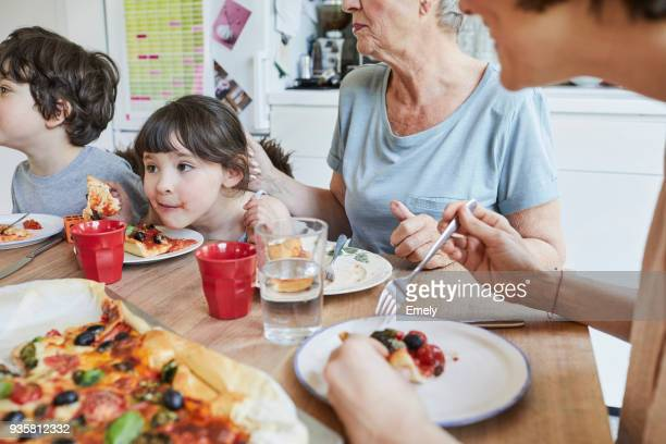 three generation family sitting at kitchen table eating pizza - comfort food stock pictures, royalty-free photos & images