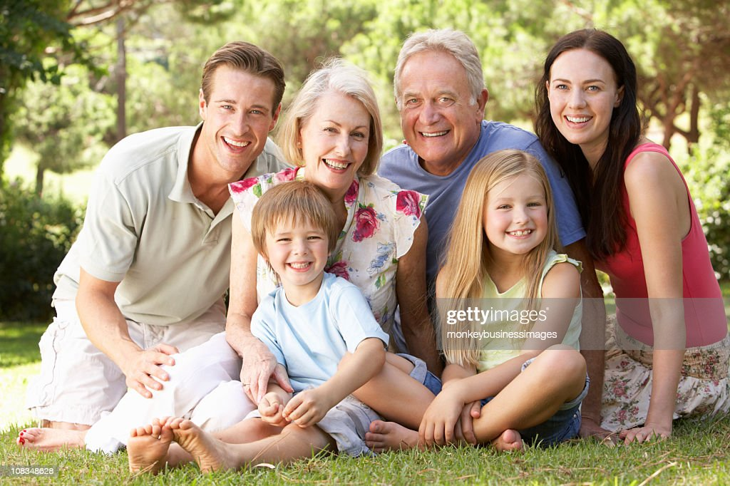 Three Generation Family Sitting In Park Together : Stock Photo