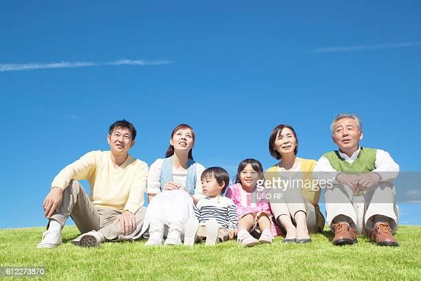 Three Generation Family Sitting on Grass