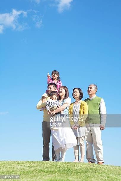 Three generation family standing on hill