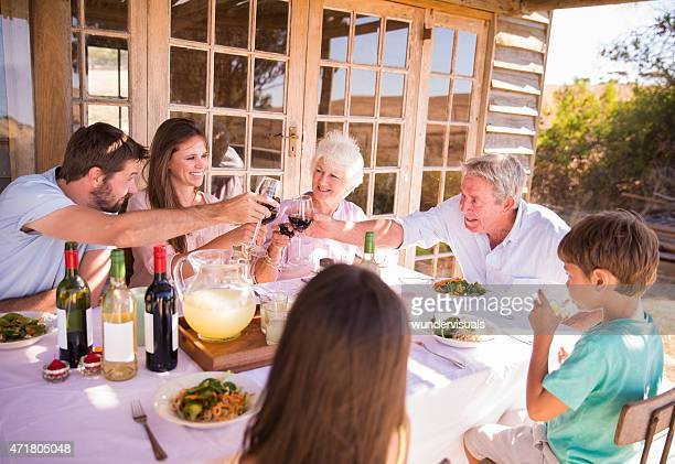 Three generation family toasting each other at a summer meal