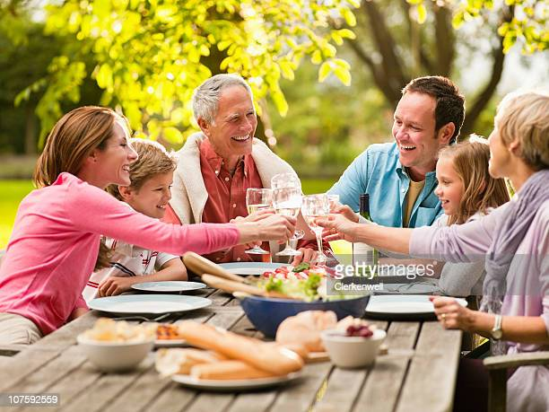 Three generation family toasting glass of wine at picnic table