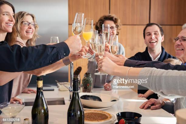 three generation family toasting with champagne at brunch celebration. - mimosa stock pictures, royalty-free photos & images