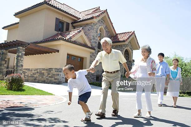 Three generation family walking by a house