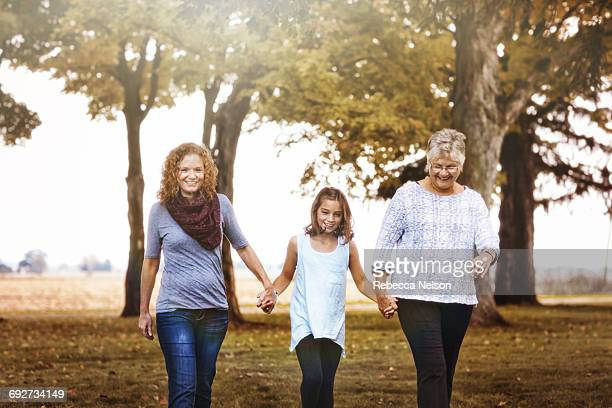 Three generation family walking in rural setting, in Autumn