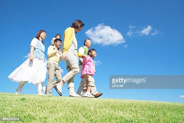 Three generation family walking on hill