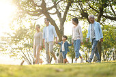 three generation family walking outdoors in park