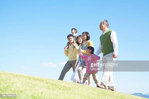 Three generation family walking up a hill