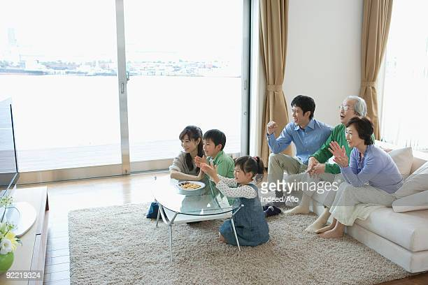 Three generation family watching television together