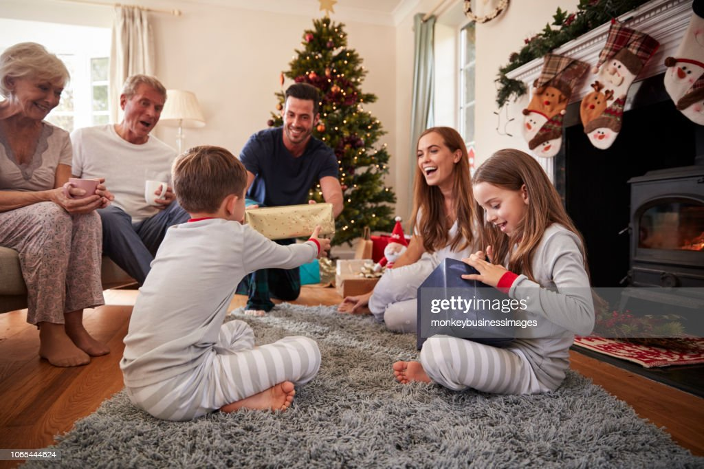 Three Generation Family Wearing Pajamas In Lounge At Home Opening Gifts On Christmas Day : Stock Photo