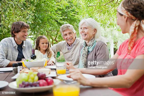 three generation family with girl (6-7 years) at garden table - 65 69 years stock pictures, royalty-free photos & images