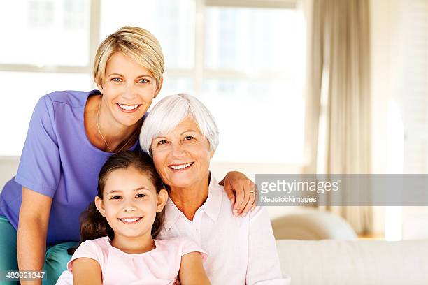 Three Generation Females Smiling Together In Living Room