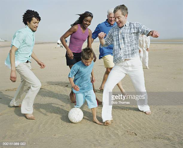 three generation group playing football on beach - grandfather stock pictures, royalty-free photos & images