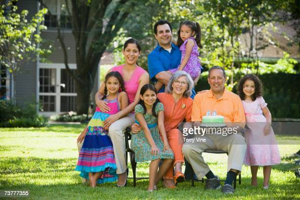 Three generation Hispanic family posing for portrait in backyard