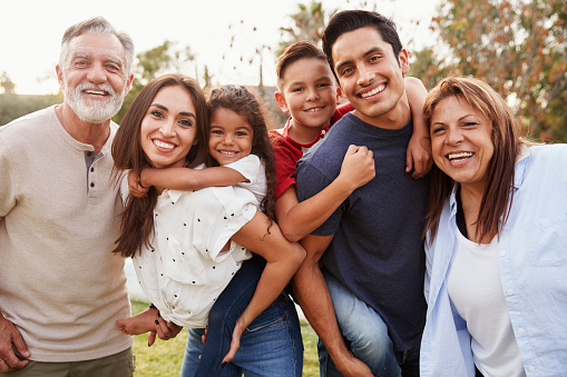 Three generation Hispanic family standing in the park, smiling to camera, selective focus 1094440264