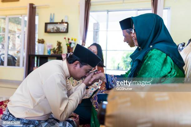 three generation malaysian family gathered for hari raya puasa at home - eid ul fitr stock pictures, royalty-free photos & images