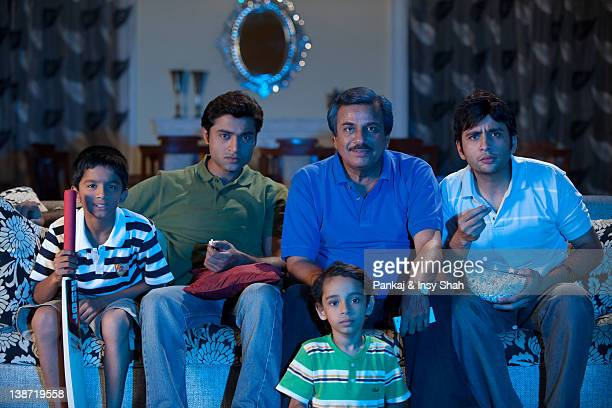Three generation male family members watching sports program in the television