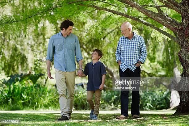 Three generation males walking in park