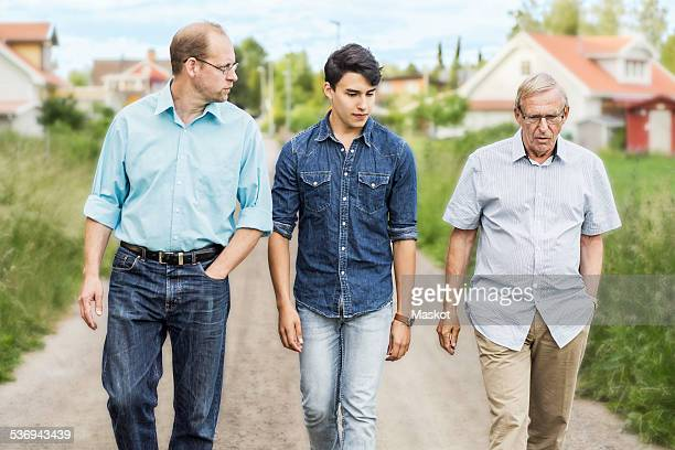 Three generation males walking together on footpath