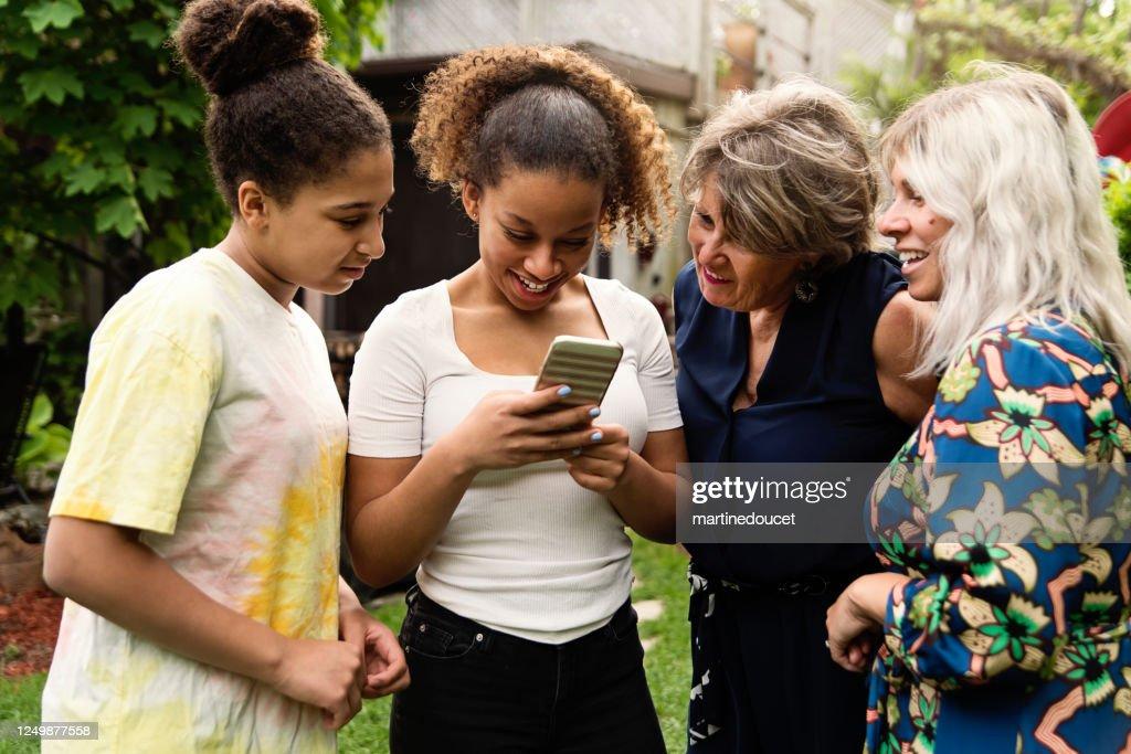 Three generation mixed-race family looking at mobile phone backyard. : Stock Photo