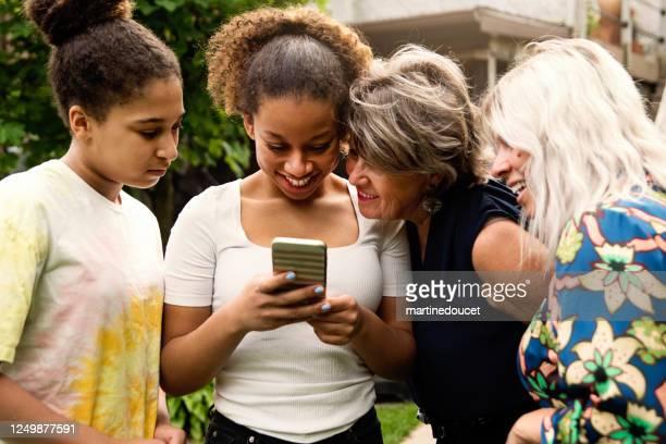 """familia de tres generaciones de carreras mixtas mirando el patio trasero del teléfono móvil. - """"martine doucet"""" or martinedoucet fotografías e imágenes de stock"""